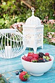 Fresh berries in a bowl on a garden table with lanterns