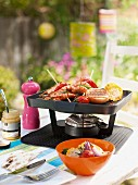 A table-top barbecue with prawn skewers and vegetables, on a garden table