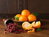 Recipe ingredients for dry cured gammon with clementines and cranberries. Whole and halved clementines with scoop of cranberries