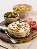Baked soft cheese with potatoes, dry-cured ham and pickled gherkins
