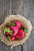Fresh strawberries on sackcloth on a wooden surface (view from above)