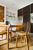 Essplatz mit Holzstühlen und Holztisch in skandinavischem Stil vor moderner dunkler Küchenschrankwand