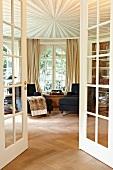 Blick durch offene Sprossentüren auf Chaiselongue am Fenster und abgehängte Decke mit strahlenförmigem Design in rundem herrschaftlichem Salon