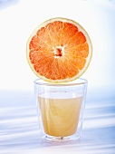Half a grapefruit on top of a glass of grapefruit juice
