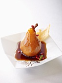 A poached pear in coffee syrup with red peppercorns