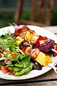 Barbecued chicken kebabs with salad on a garden table