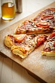 Pizza with salami, tomatoes and mushrooms on a wooden board