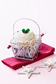 Christmas cupcake in a little silver basket and a star-shaped tealight
