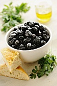 Schwarze Oliven in einer Schale mit Brot und Petersilie