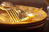 Golden forks on stacked gold plates