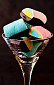 Colourful marshmallows with chocolate glaze in a glass against a black background