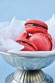 Raspberry macaroons with chocolate filling in a pewter dish