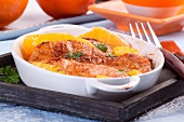Chicken breast with oranges in a baking dish