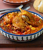 Duck Cassoulet, in colourful dish, on a chopping board