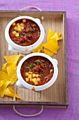 Chilli con carne with cubes of cheese, served with tortilla chips