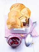 Buchteln (baked, sweet yeast dumplings) with nougat filling and raspberry sauce