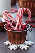 Candy canes and decorative wreath of berries in copper jelly mould