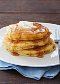 A Stack of Cornmeal Pancakes with Butter and Maple Syrup