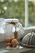 Brown eggs in a storage jar and a wicker cover on the windowsill
