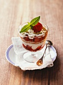 Parfait with a sponge cake, strawberries and pistachios