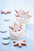 Gingerbread stars garnished with icing in a wooden box and around it
