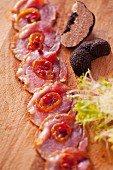 Venison Carpaccio marinated with truffles and garnished with caramelized onion