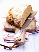 Whole wheat and rye bread on a cutting board with a bread knife