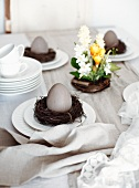Easter table set with spring flowers, Easter eggs, crockery and napkins