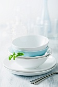Stacked dinner bowls and plates, drinking glasses and forks