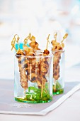 Chicken satay skewers with honey in glasses