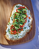 A slice of bread topped with goat's cheese, tomatoes, cucumber and cress