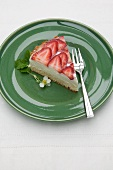 A slice of quark cake with fresh strawberries