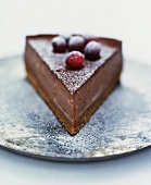 A piece of chocolate cheesecake with cranberries