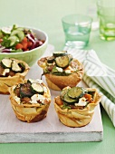 Mini tartlets filled with sweet potato, vegetables, sausage and feta
