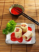 Sweet pudding rice rolls with rhubarb in strawberry sauce