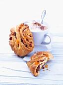 Brötchen mit Trockenfrüchten und Milchkaffee