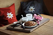 Plate of nut pastries, cups of tea and sugar crystals on wooden tray with hand-stitched leather handles; edelweiss cushions in background