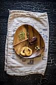 Getrocknete Dattel und Apfelringe mit Gewürzen auf einem Holzteller