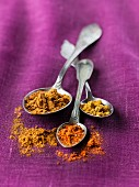 Assorted types of curry powder on old silver spoons on purple material