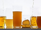Assorted clear and cloudy apple juices in glasses