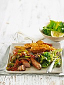 Sausages with braised peppers and potato wedges
