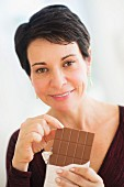 A woman holding a bar of chocolate