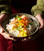 Hands holding a dish of vegetable rice with prawns