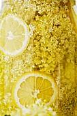 Home-made elderflower juice with slices of lemon in a storage jar