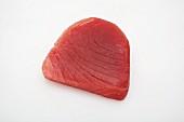 Raw tuna steak on a white surface