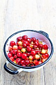 Sweet cherries in colander on a wooden table