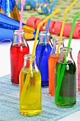 Colourful drinks in bottles with drinking straws