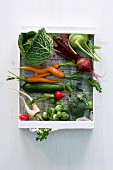A wooden box of fresh vegetables (brassicas, root vegetables and a cucumber)