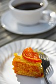 A slice of orange cake with a cup of coffee