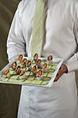 Kellner hält ein Tablett mit Asia-Wraps auf Gurkenstreifen